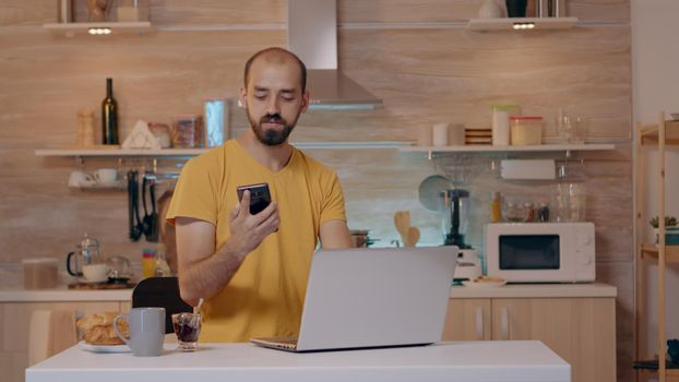 Man sitting in kitchen switch off the lights using voice command