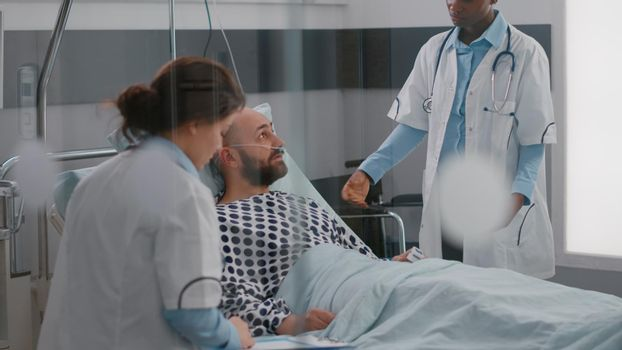 Patient discussing with doctors while lying in bed during sickness recovery