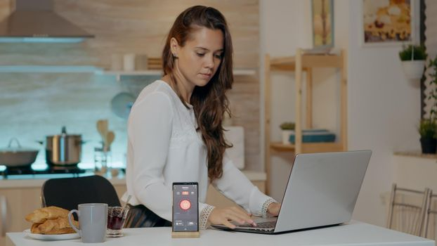 Freelancer working from home turning on lights using voice command