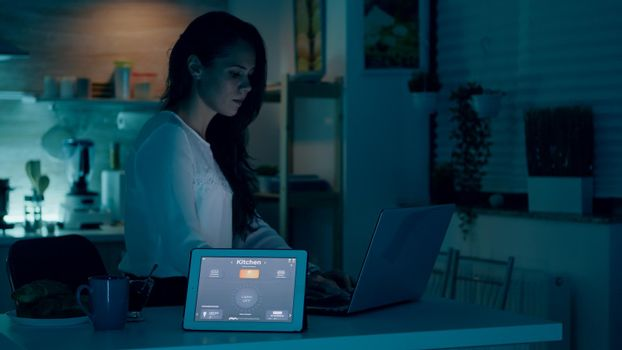 Remote woman working in modern house giving voice command to tablet