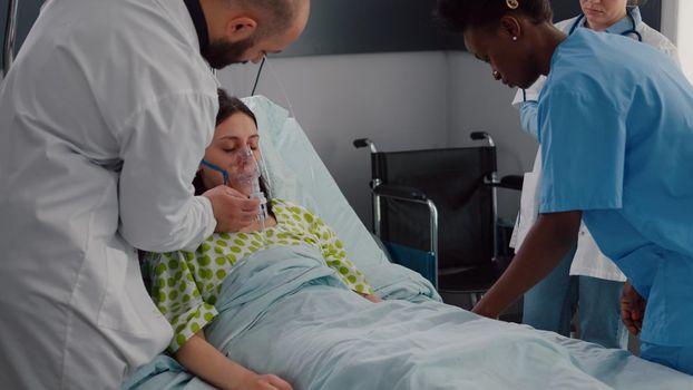 Clinical team monitoring sick woman putting oxigen mask analyzing respiratory sickness