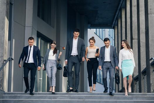 Confident team members walking on stairs. Business men and women in formal suits go and talk on the background of modern office building.