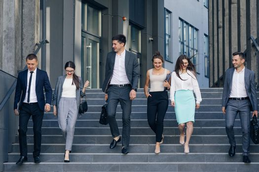Confident team members walking on stairs. Business men and women in formal suits go and talk on the background of modern office building