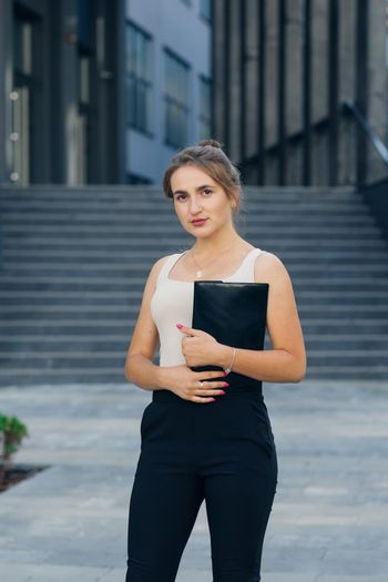 Portrait of a young businesswoman. Successful businesswoman standing outdoors near office building.