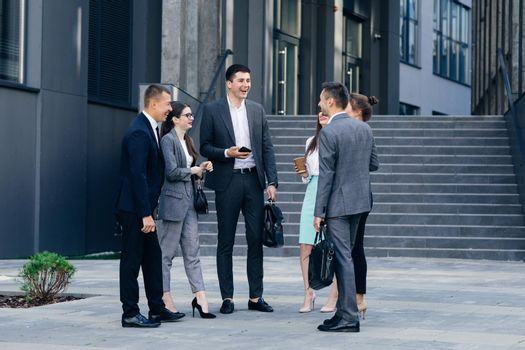 Male and Female Business People Discuss Business. Group of six young caucasian business people men and women meeting discussing outside office building