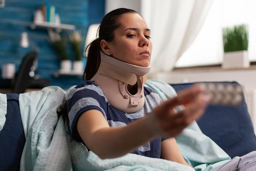 Woman with sickness and cervical foam collar on couch