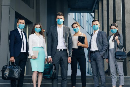 Corporate team portrait in Protective Mask. Professional business people in Protective Mask look at camera standing outside business center.
