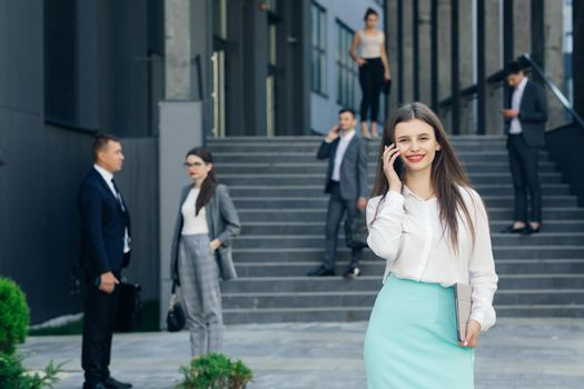 Beautiful young businesswoman wearing white shirt using modern smart phone. Professional female employer typing text message on cellphone outside