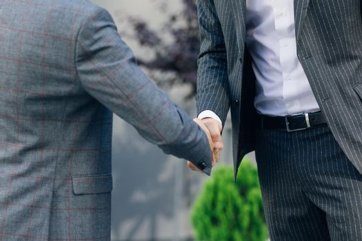Hands of Top managers in Business Suits, shake hands with each other at Business center background. Agree to a deal or say hello. Unrecognizable person.