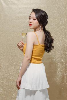Feminine asian model raising glass of champagne standing over sparkles background