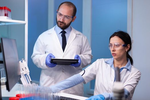 Professional team of medical researchers working together in sterile lab