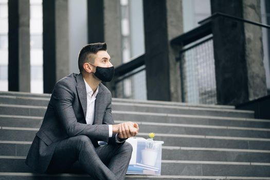 Unemployed businessman lost his business. Anxious concept. Workless man in despair. Fired male office worker in medical mask sitting on stairs in depression with box of stuff