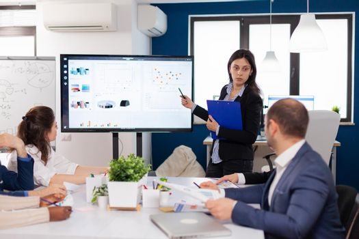 Young team leader in big corporation briefing coworkers