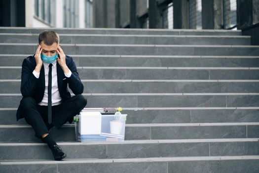 Fired male office worker in medical mask sitting on stairs in depression with box of stuff. Anxious concept. Workless man in despair. Unemployed businessman lost his business