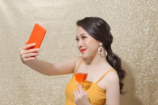 Image of cute alluring woman holding glass of champagne while taking selfie photo isolated over sparkles wall.