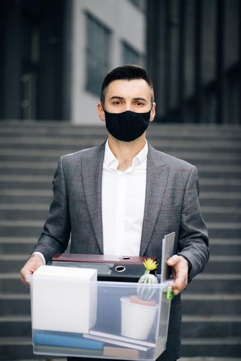 Young businessman in medical mask carries box with personal belongings leaving the office. Lack of jobs. Financial crisis. Unemployment