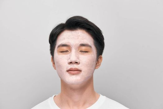 young man has mud clay mask on face