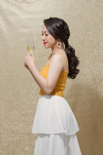 Indoor shot of positive attractive young female in evening dress with glass of champagne,