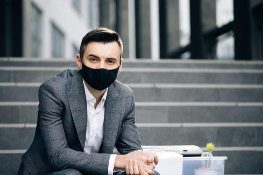 Sad young businessman in medical mask sitting on the stairs near office building. Feeling bad and annoyed. Unemployed businessman lost his business. Anxious concept. Workless man in despair