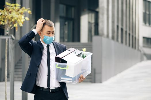 Young sad businessman in protective face mask with box of stuff as leaving business center. Unemployment rate growing due pandemic. Male office worker lost her job