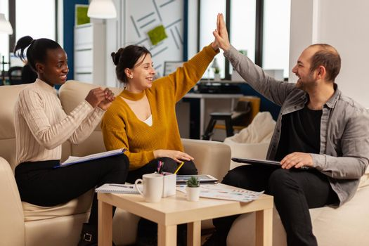 Diverse employees business team give high five together