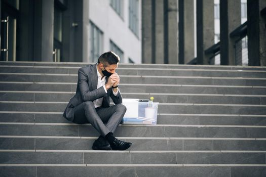 Fired male office worker in medical mask sitting on stairs in depression with box of stuff. Unemployed businessman lost his business. Anxious concept. Workless man in despair