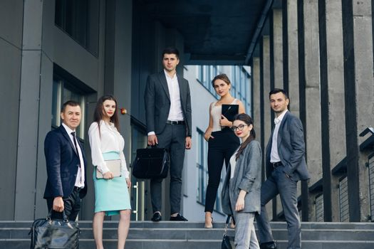 Portrait of successful creative businessman and businesswoman wear formal suits looking at camera and smiling in modern office workplace. Diverse male and female standing together