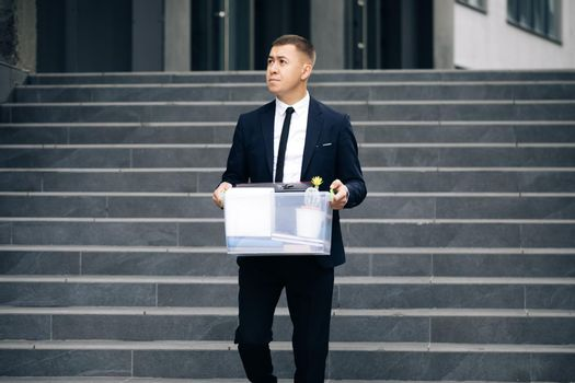 Male office worker in depression with box of personal stuff. Left without money. Businessman lost job. Fired man walking outdoor. Depressed jobless person. Unemployment concept
