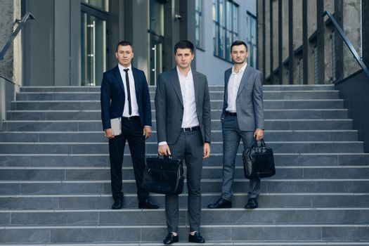 Three successful and confident businessman standing on the steps. Businessmen in suit. Successful work.