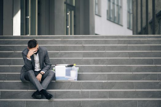 Fired caucasian male office worker in medical mask sitting on stairs in depression with box of stuff. Anxious concept. Workless man in despair. Unemployed businessman lost his business