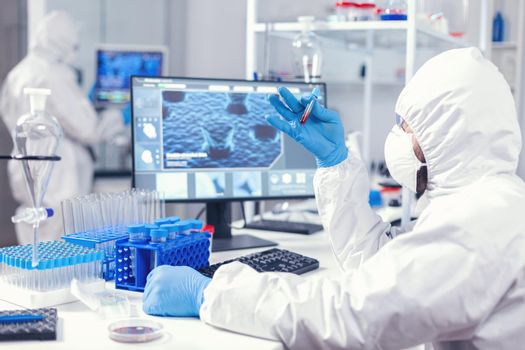 Scientist in sterile chemistry suit analysing blood sample