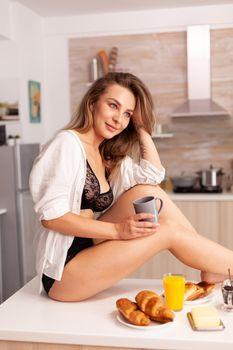 Dreamy lady enjoying morning coffee in kitchen