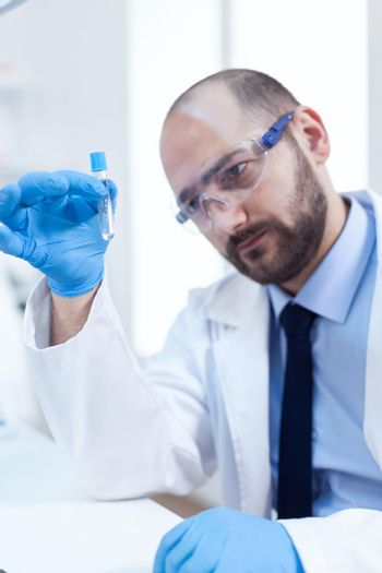 Male scientist with sterile gloves looing at test tube