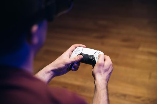 Closeup of man's hands playing video games on gaming console in front of TV widescreen. Man play with Play station 5 Dual Sense controller. Colorful lights.
