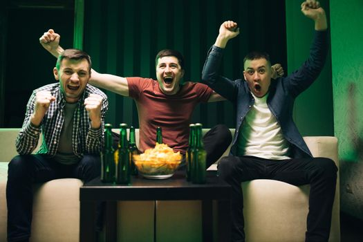Cheerful happy Caucasian guys cheering for favorite team. Loyal football fans supporting their team. Men watching TV with sport channel late at night and drinking beer