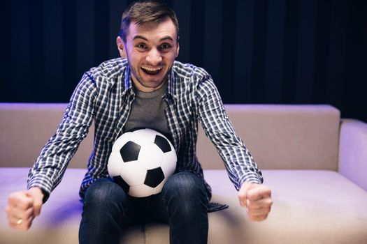 Fun guy 30s football fan cheer up support favorite team hold soccer ball in t-shirt in dark living room. People emotions sport leisure lifestyle. Sports Fan Reaction Concept