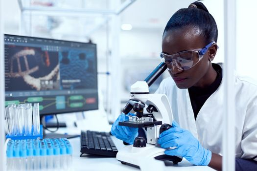 Virologist of african ethnicity sitting at her workplace neat test tubes