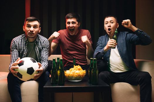 Young male sport fans shout watching football game together at home. Expressing, screaming and emotion. Loyal football fans supporting their team