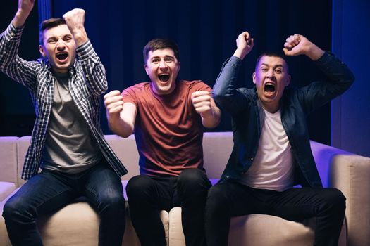 Happy young male sport fans shout watching football game together at home. Expressing, screaming and emotion. Loyal football fans supporting their team