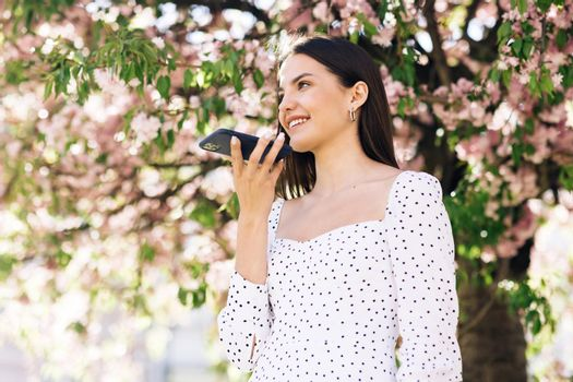 Happy young girl using smart phone voice recognition, dictates thoughts, voice dialing message outdoor talking to mobile assistant. Talking mouth in the speaker of a young woman