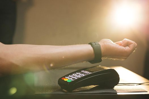 Person pays in a cafe using an electronic smartwatch. Contactless technology NFC. Consumerism internet online purchases. Man is Paying with a Smart Watch