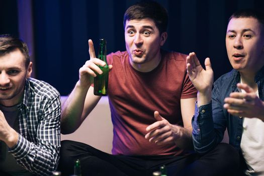 Men watching TV with sport channel late at night and drinking beer. Cheerful happy Caucasian guys cheering for favorite team. Loyal football fans supporting their team
