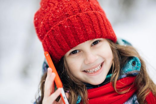 Close up of young beautiful woman in winter hat talking emotionally and surprised talking on cell phone.