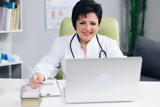 Female doctor making online video call consulting patient. European woman therapist talking to camera in remote chat. Telemedicine, telehealth. Modern medecine concept.