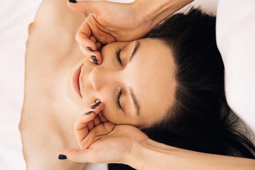 Cosmetologist making skin care procedure in beauty salon, portrait of girl closeup. Beautician doctor is applying facial cleansing foam on woman's face massaging skin in cosmetology clinic