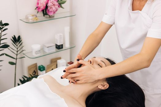 Wellness, stress relief and rejuvenation concept. Relaxed woman lying on spa bed for facial and head massage spa treatment by massage therapist in a luxury spa resort