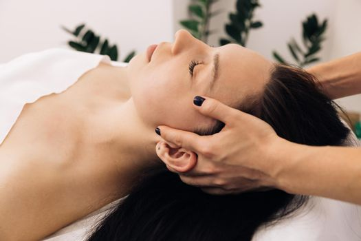 Beautician doctor is applying facial cleansing foam on woman's face massaging skin in cosmetology clinic. Cosmetologist making skin care procedure in beauty salon, portrait of girl closeup