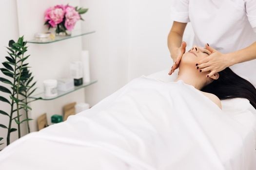 Relaxed woman lying on spa bed for facial and head massage spa treatment by massage therapist in a luxury spa resort. Wellness, stress relief and rejuvenation concept