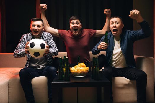 Loyal football fans supporting their team. Young male sport fans shout watching football game together at home. Expressing, screaming and emotion