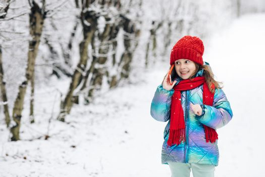 Young beautiful child girl in winter hat talking emotionally and surprised talking on cell phone. Young curly girl talking on her mobile phone while walking in the winter city street